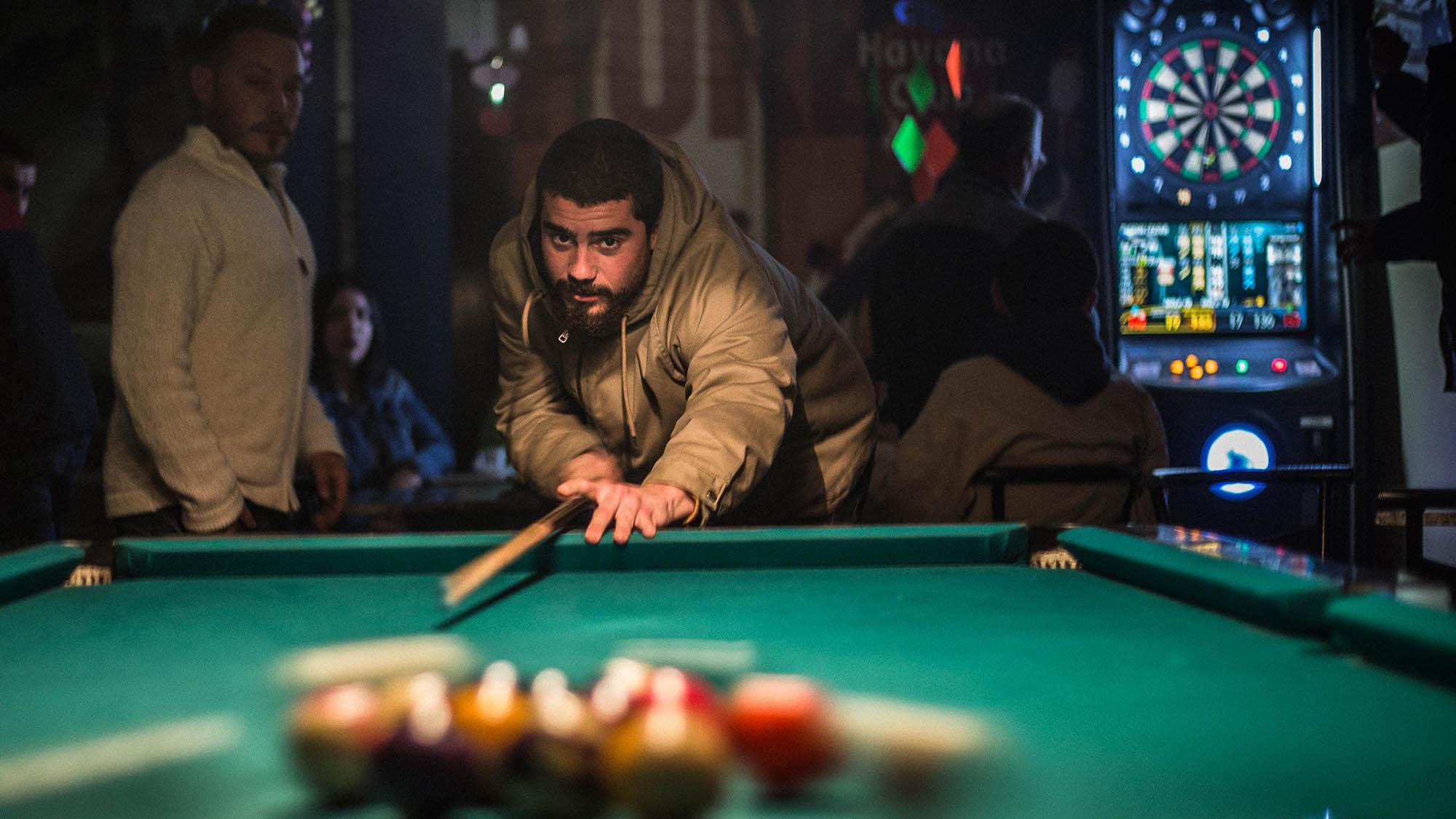 Man Playing Pool in Bar