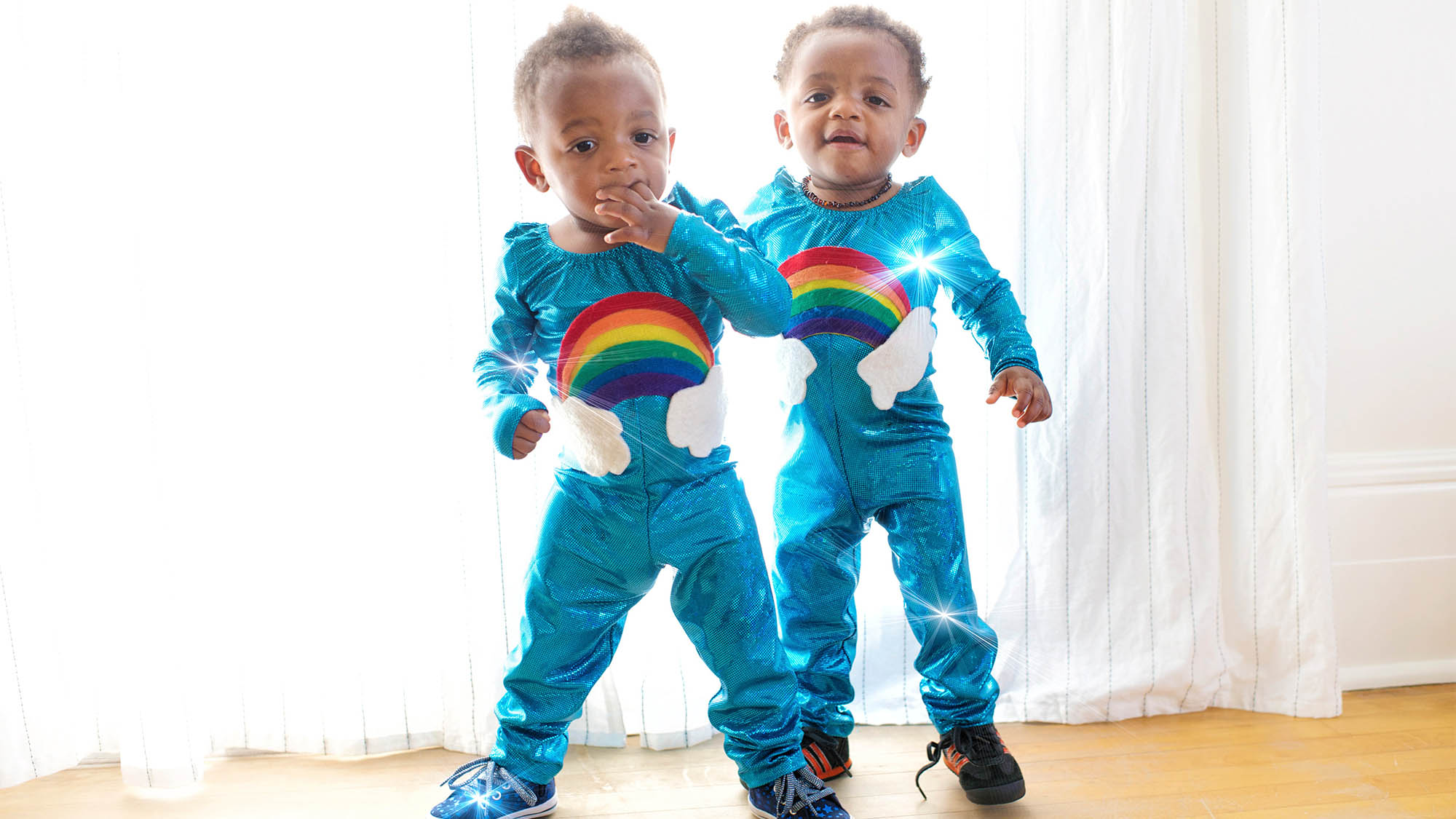Two Toddler Boys Dressed in Matching Blue Jumpsuits with Rainbows