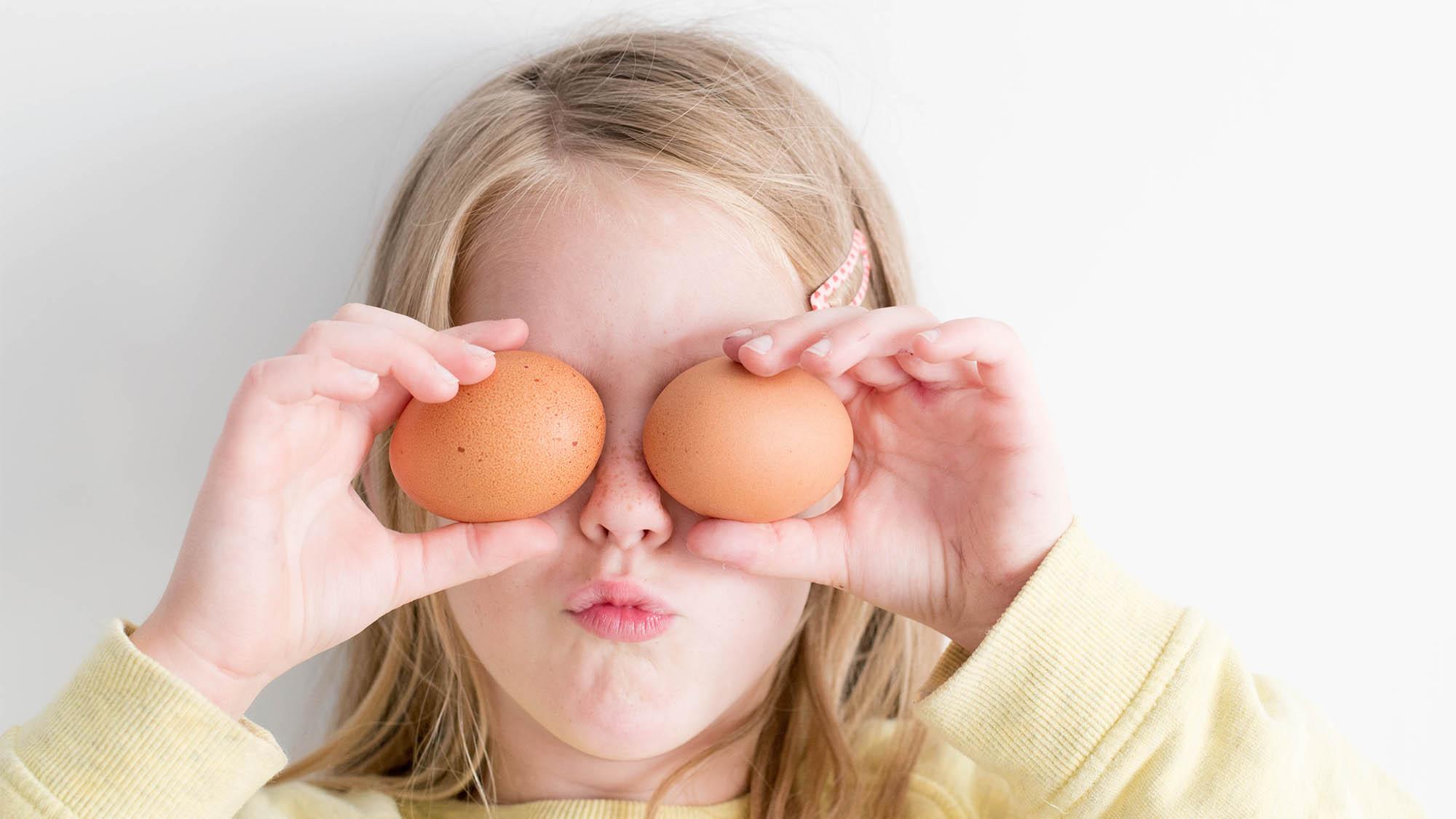 Little Girl Holding Two Eggs Over Her Eyes