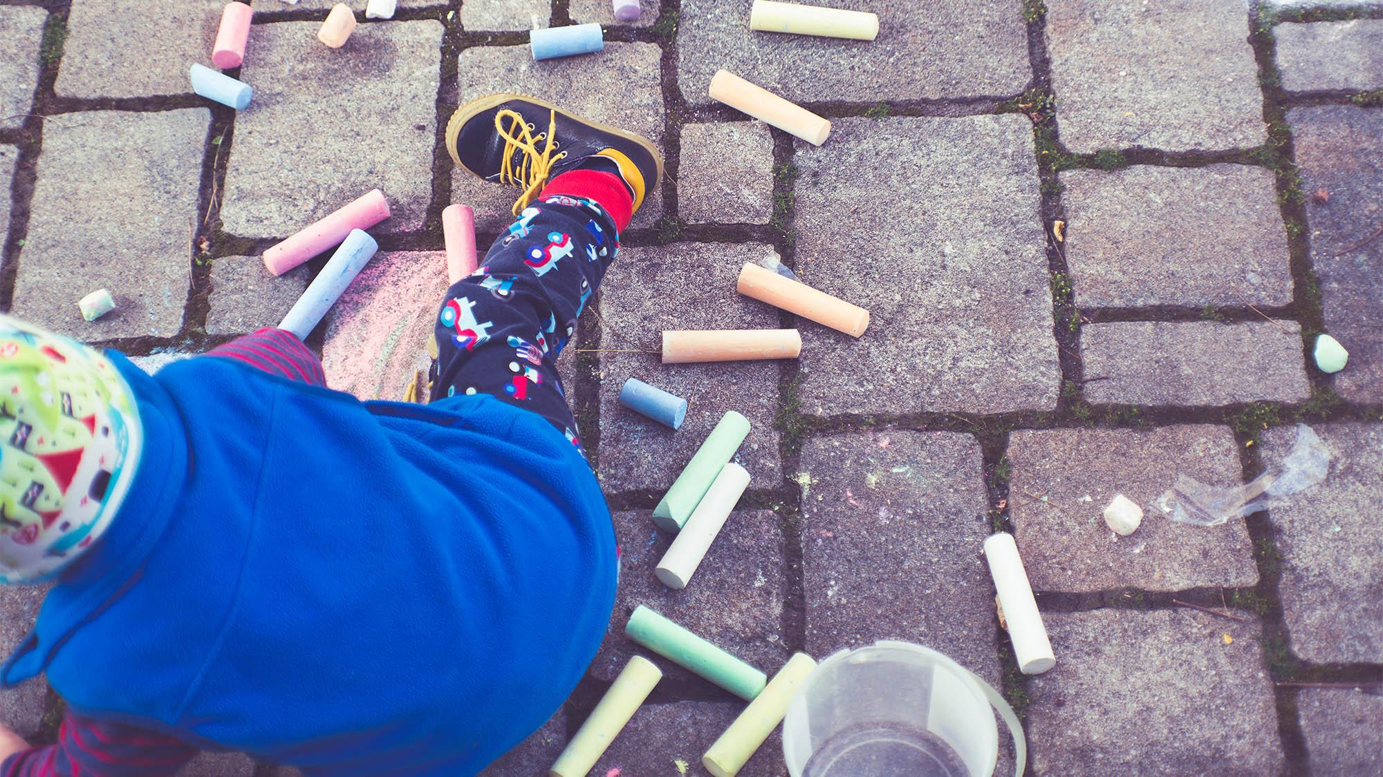 Little Boy Drawing with Chalk on Bricks