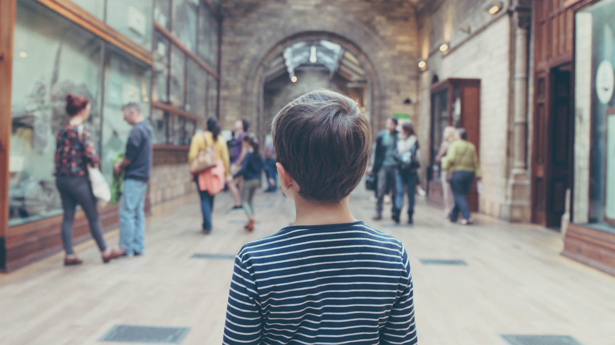 Boy Walking Through Museum from the Back