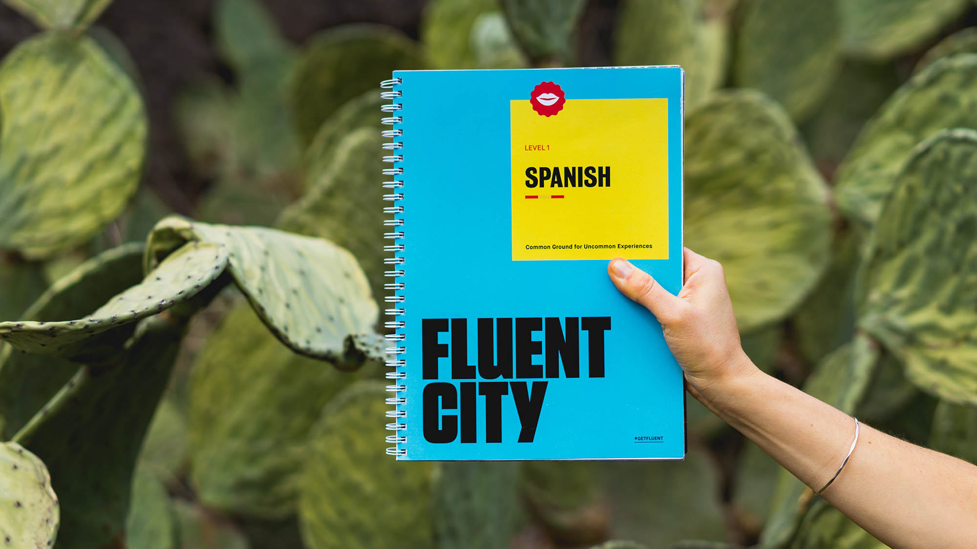 Arm Holding Blue Fluent City Spanish Language Book with Cactus Background