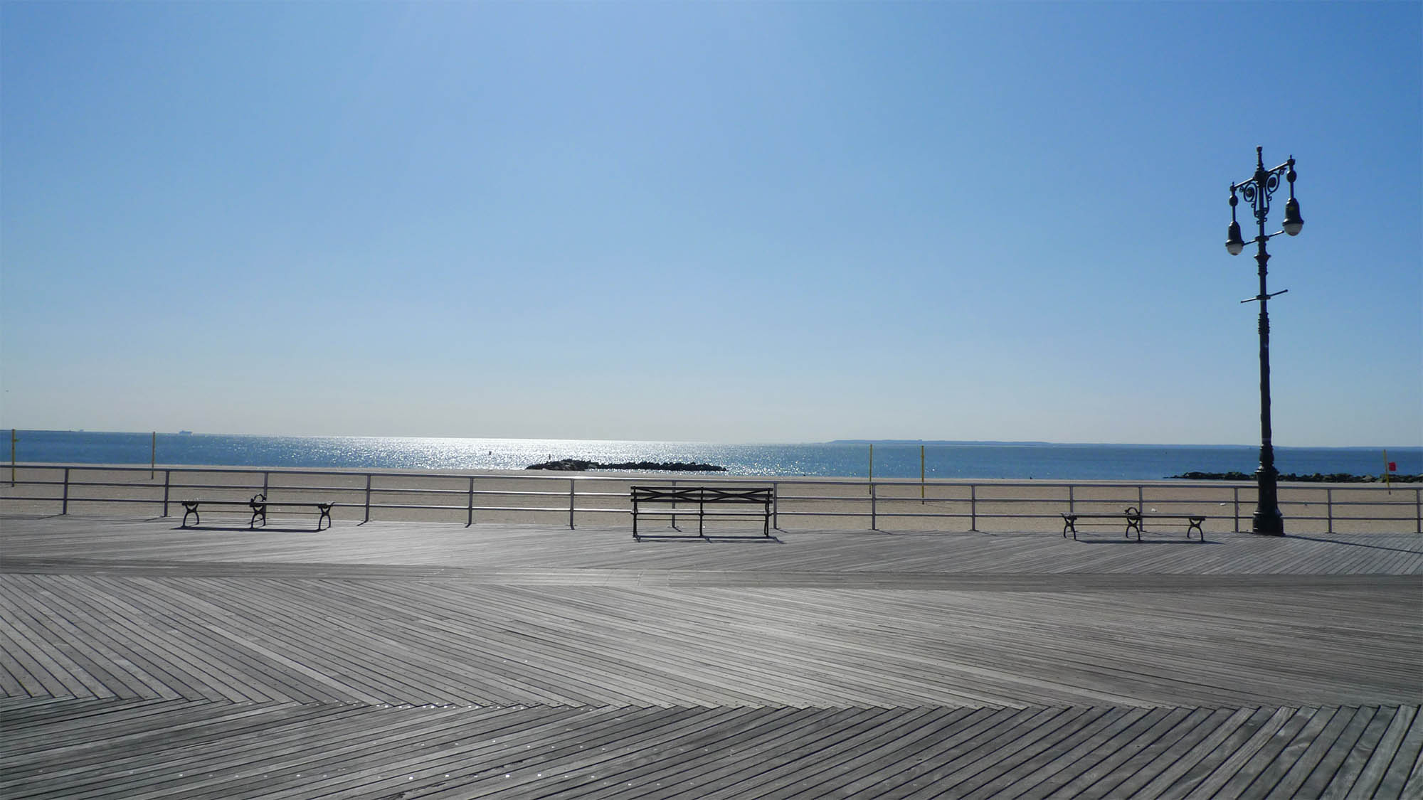 Vacant Coney Island Boardwalk with bench overlooking ocean