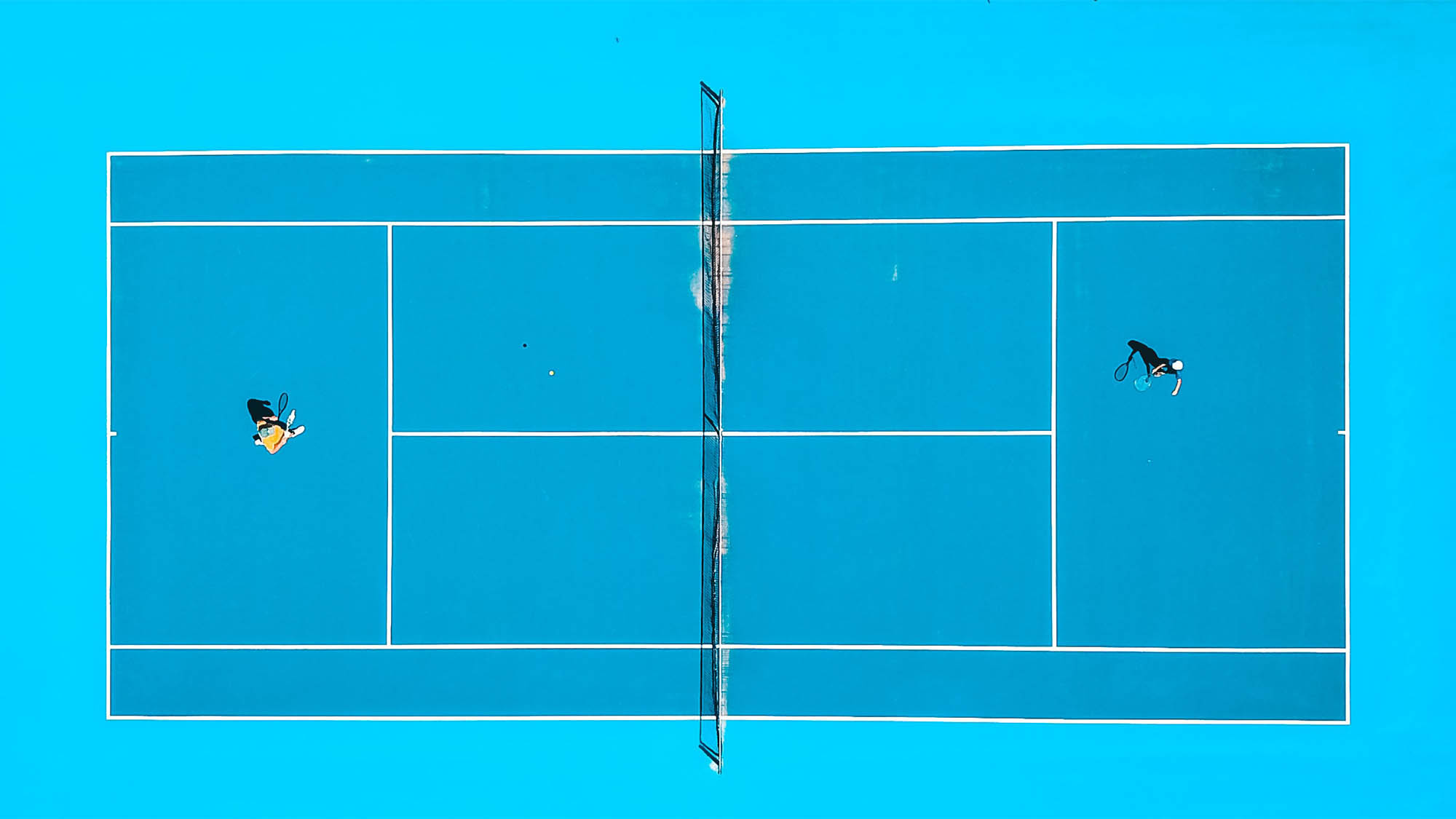 Aerial shot of two people playing tennis on teal court