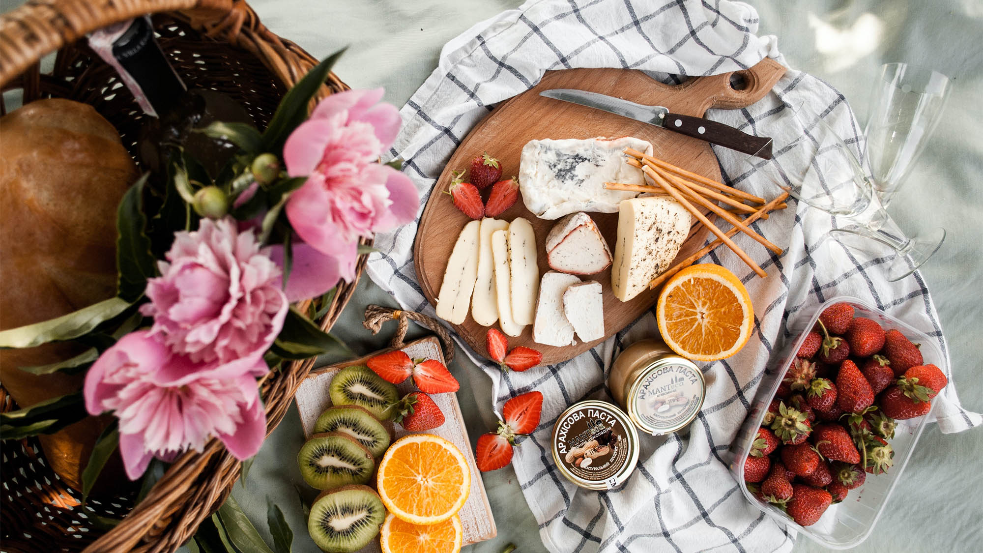Charcuterie Board Atop Picnic Blanket with Flowers and Fruit