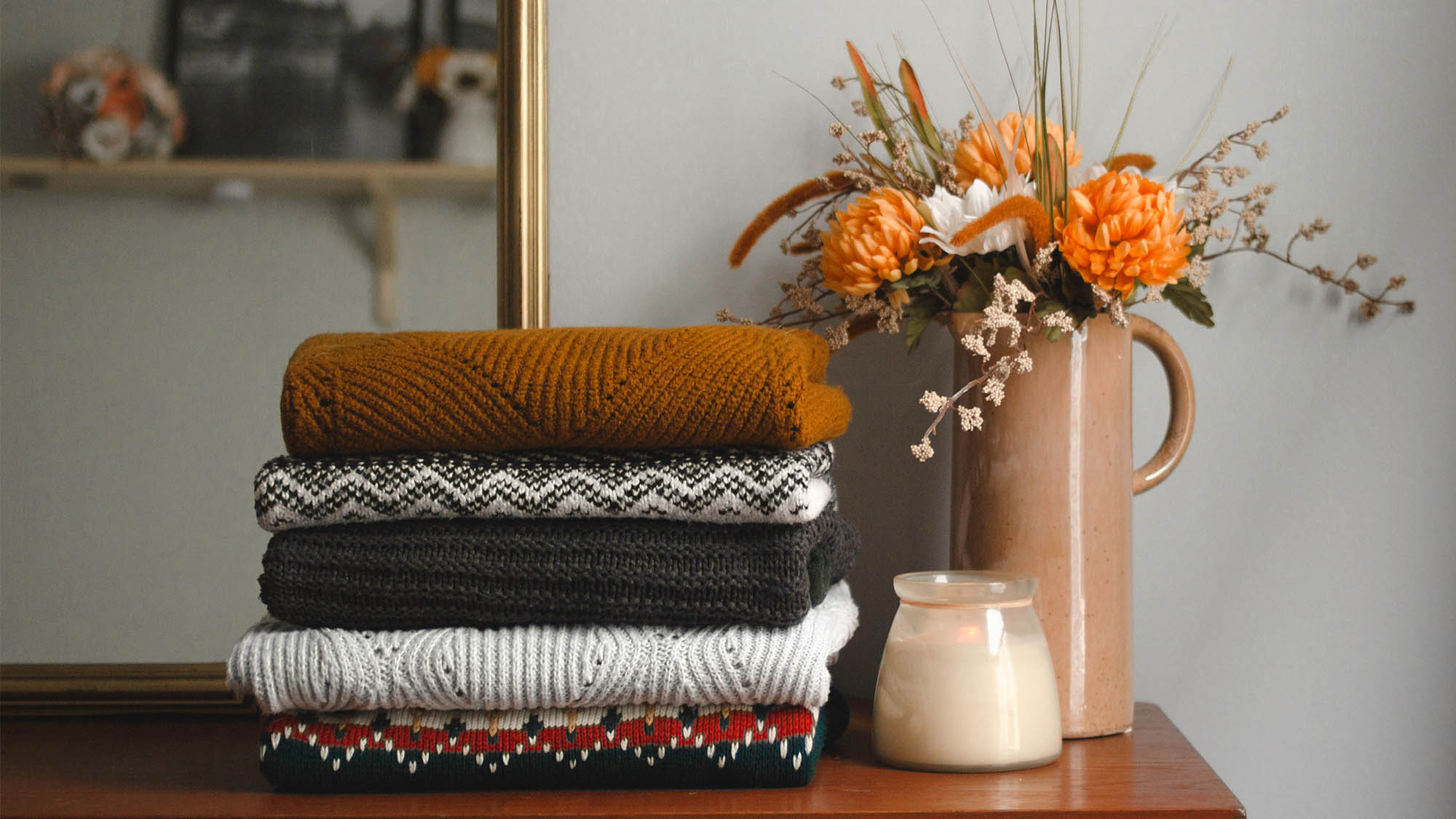 Five folded sweaters stacked on a dresser next to candle and vase with orange flowers