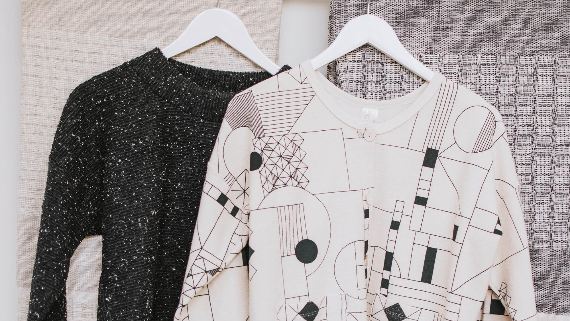 Black knit sweater hanging beside white sweater with geometric print