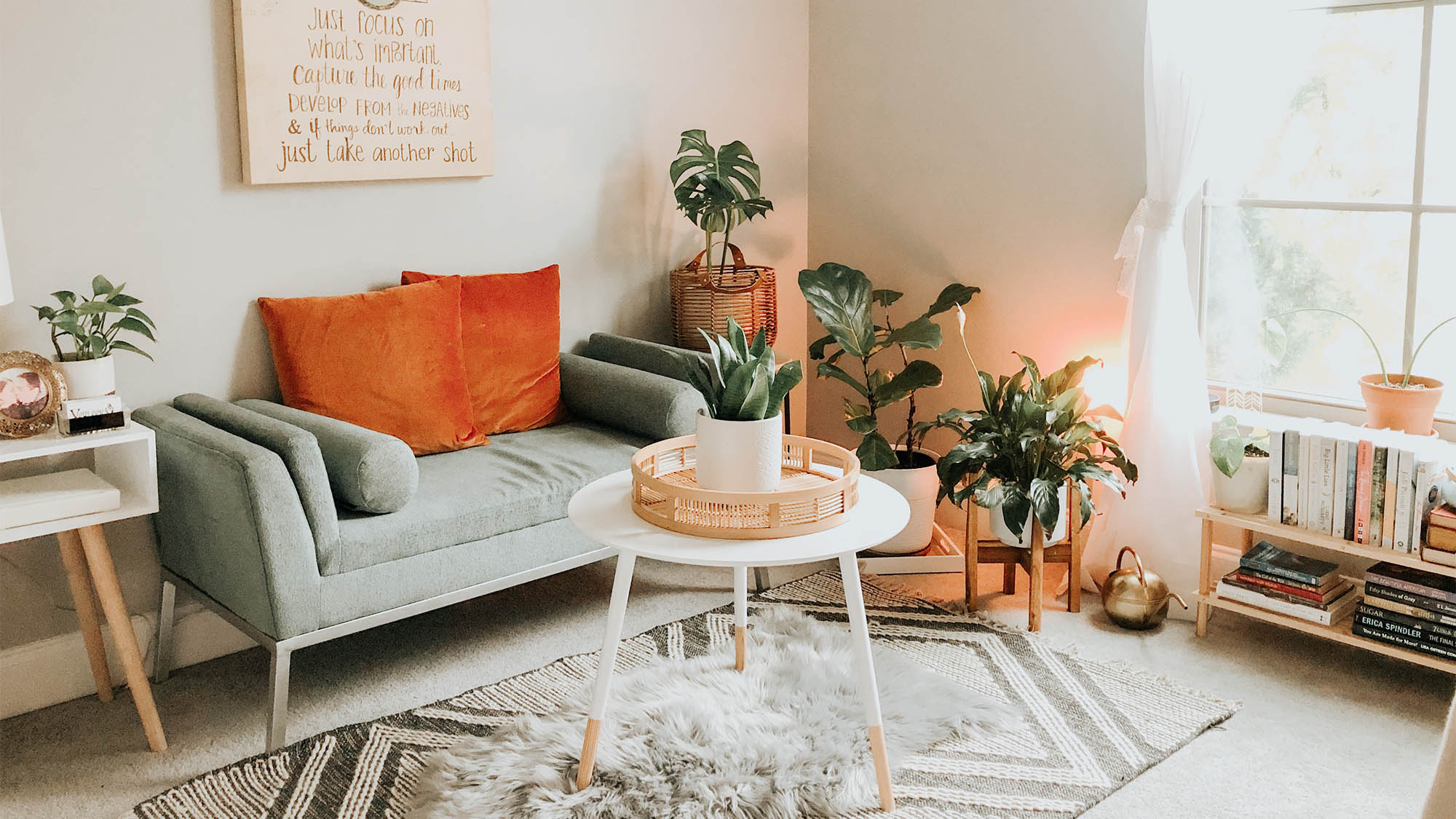 Sun-filled living room decorated with plants, gray couch and orange pillows, white table and small shag rug