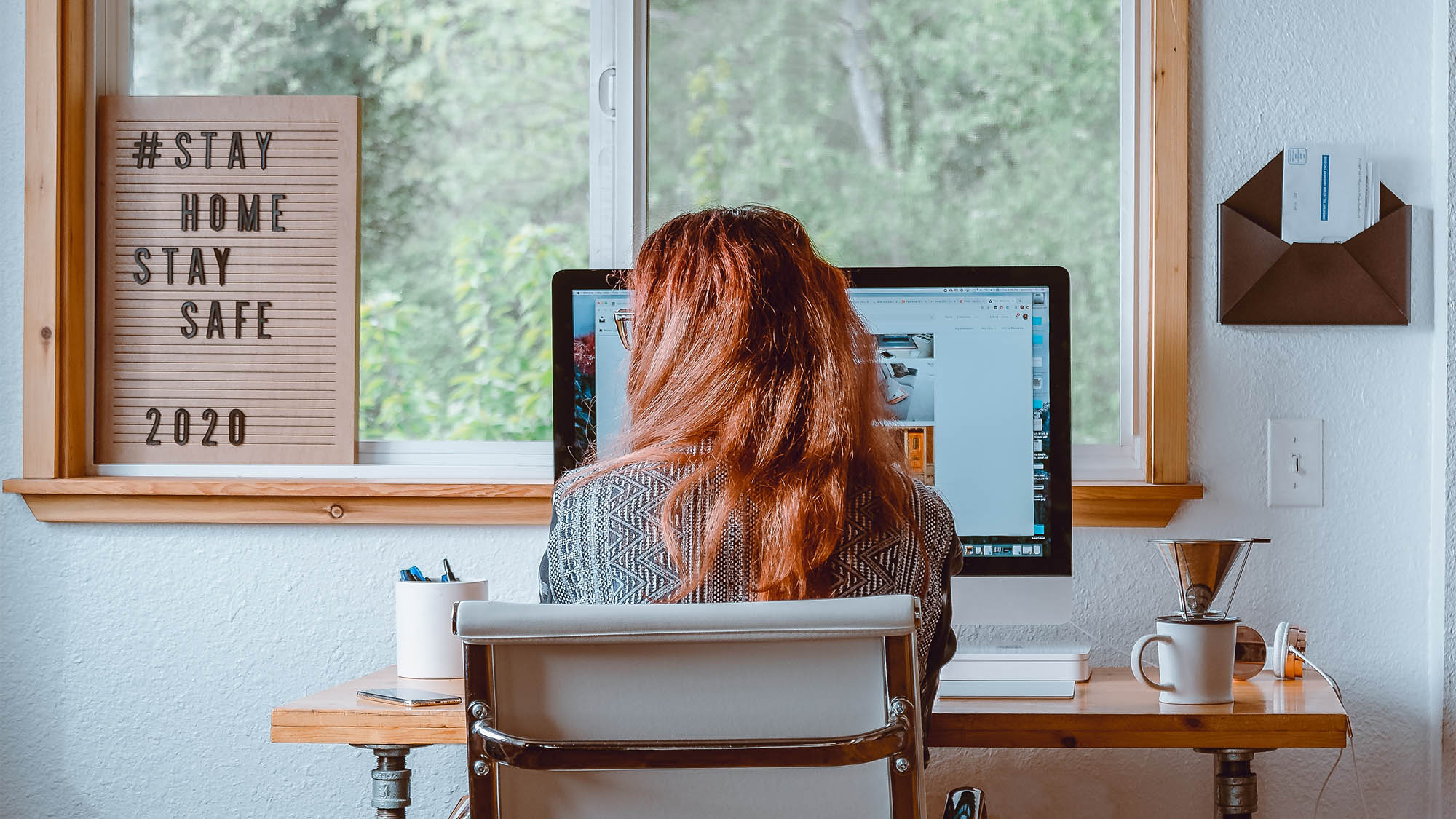Back of Long Redheaded Woman Seated at Home Office Desk with Window in Background