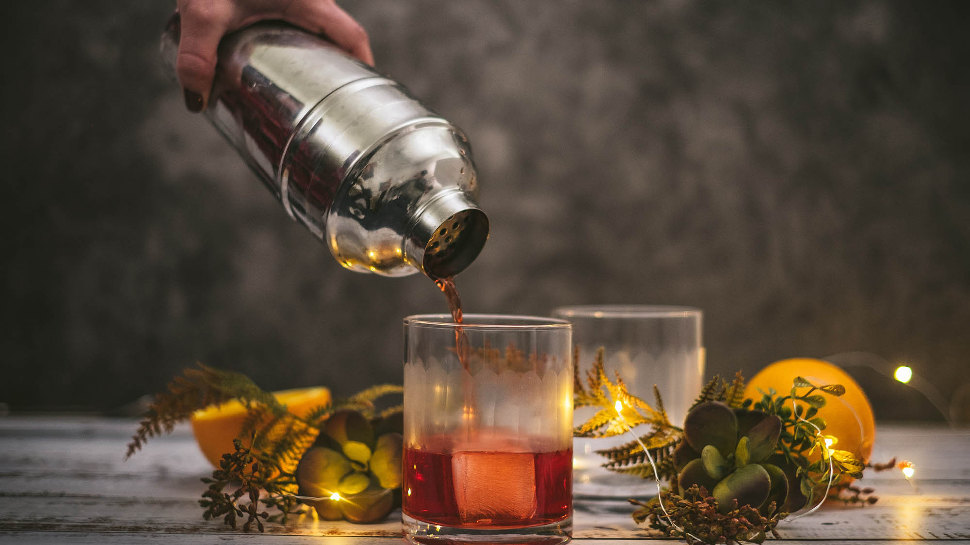 Negroni being poured from metal shaker into glass with ice cube amid sparkling lights and succulents