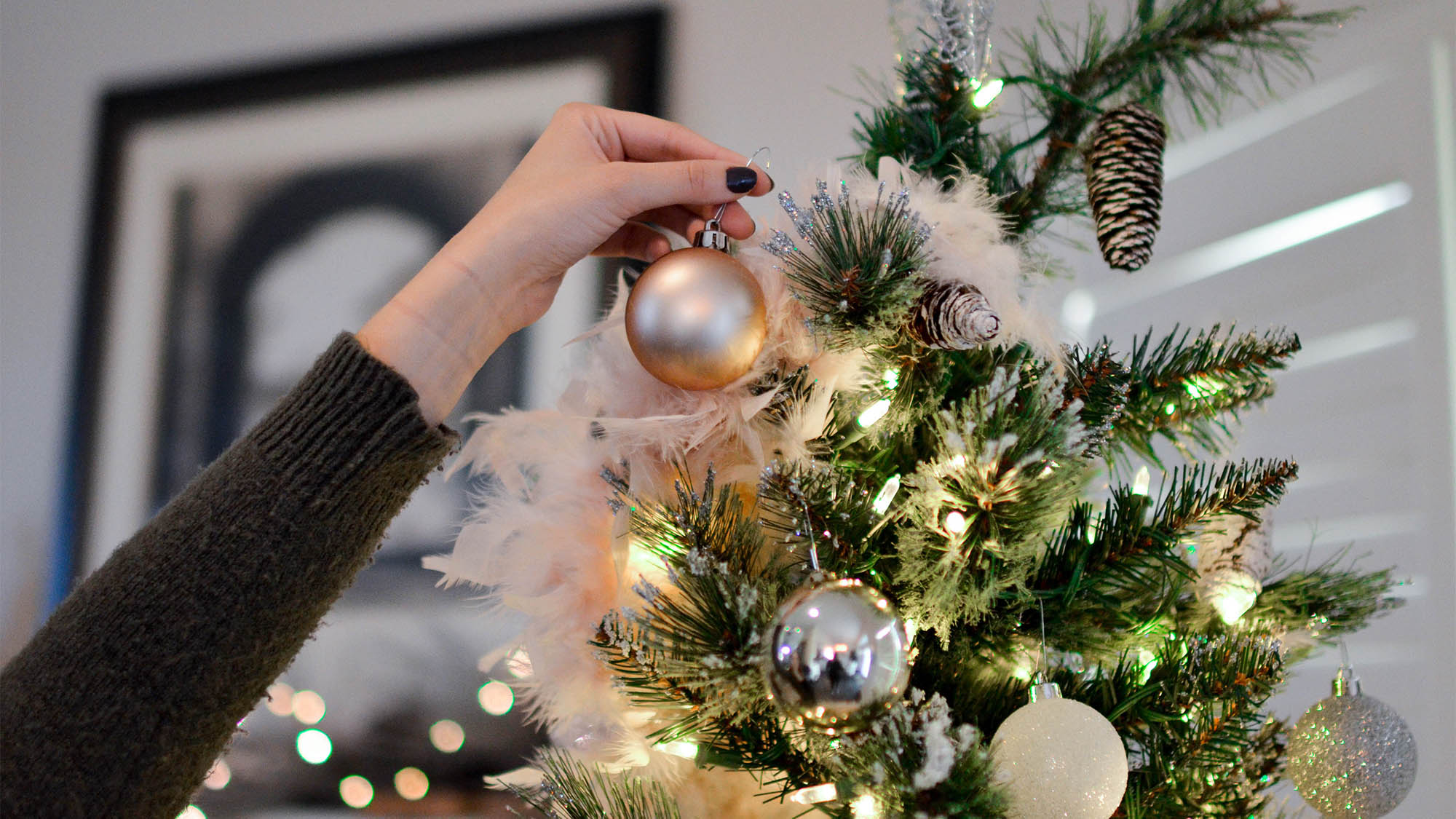 White woman's hand putting glass ornament on decorated Christmas tree