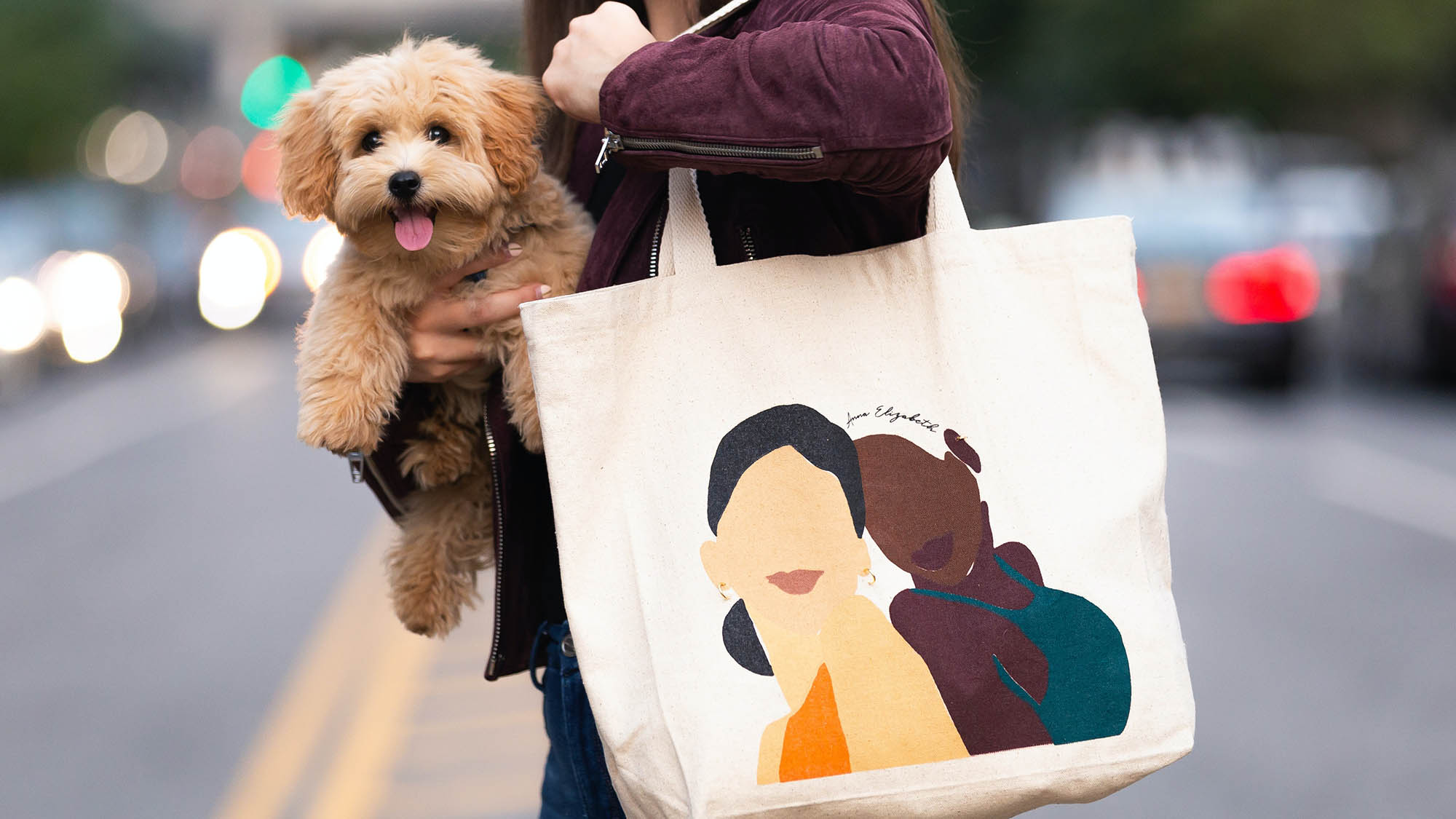 Woman on NYC street holding brown puppy and tote bag with two illustrated women