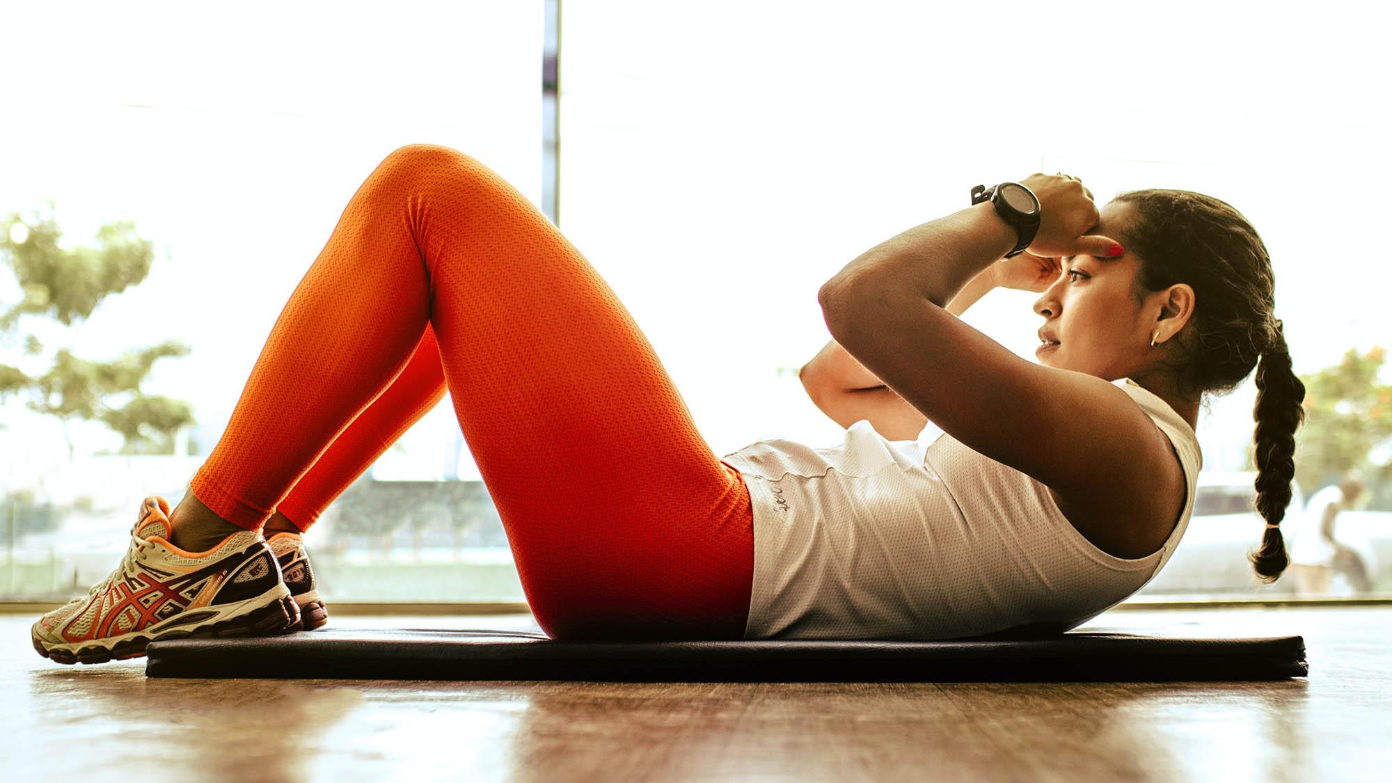 Woman doing crunch on yoga mat