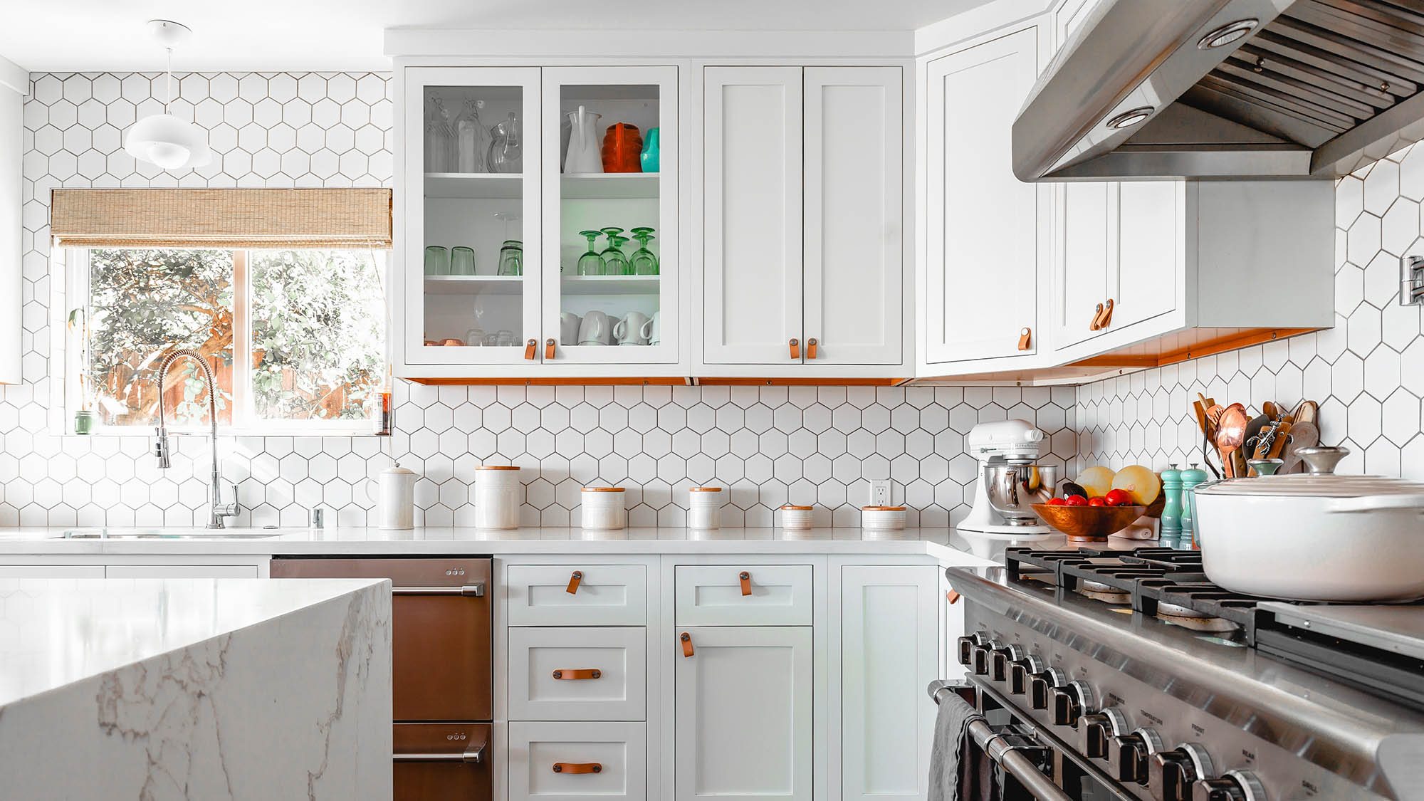 White tiled kitchen with white cabinets and leather pulls