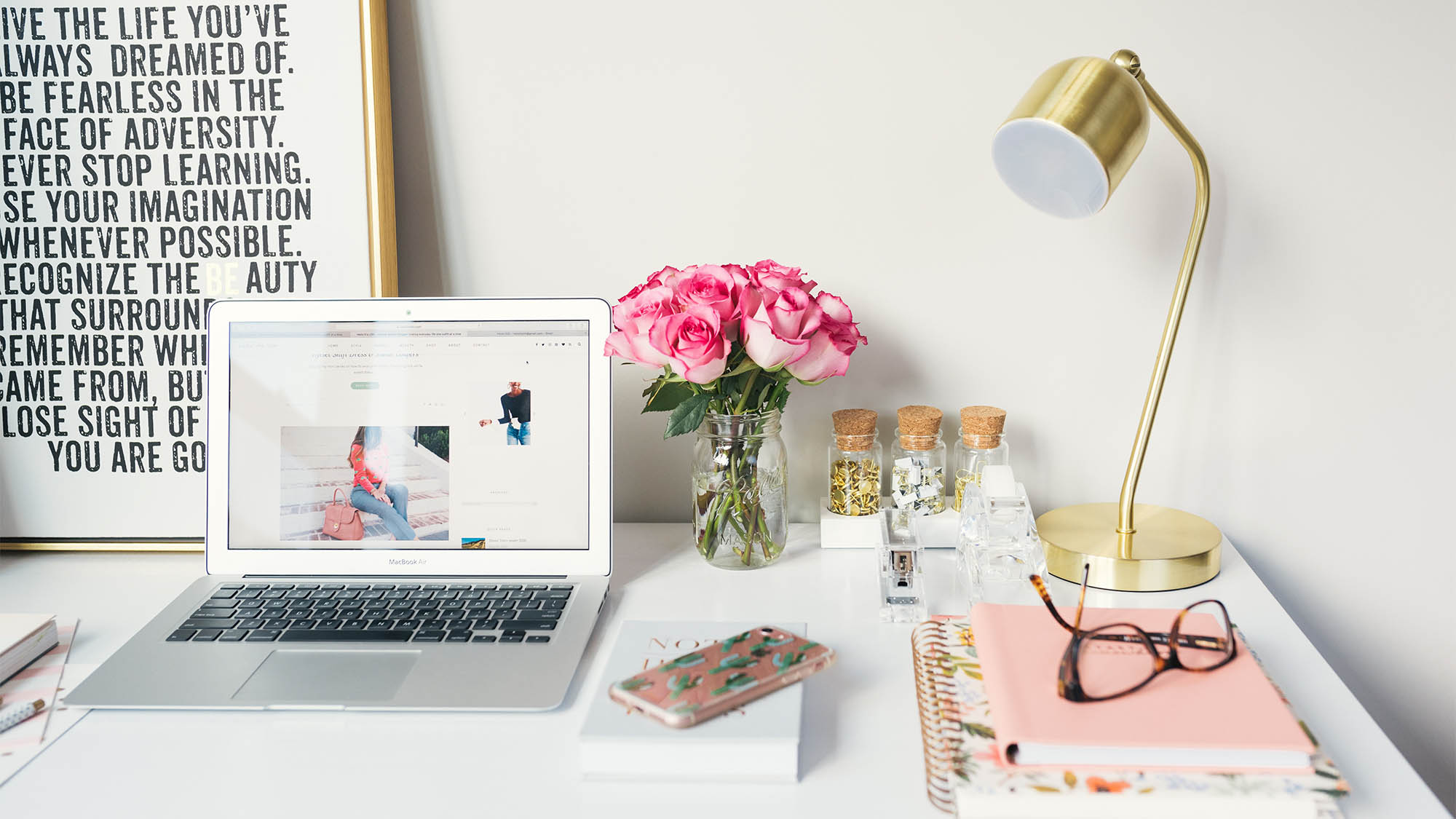 White desk with Macbook, pink roses, pink notepad and pink iPhone, framed art with words in background