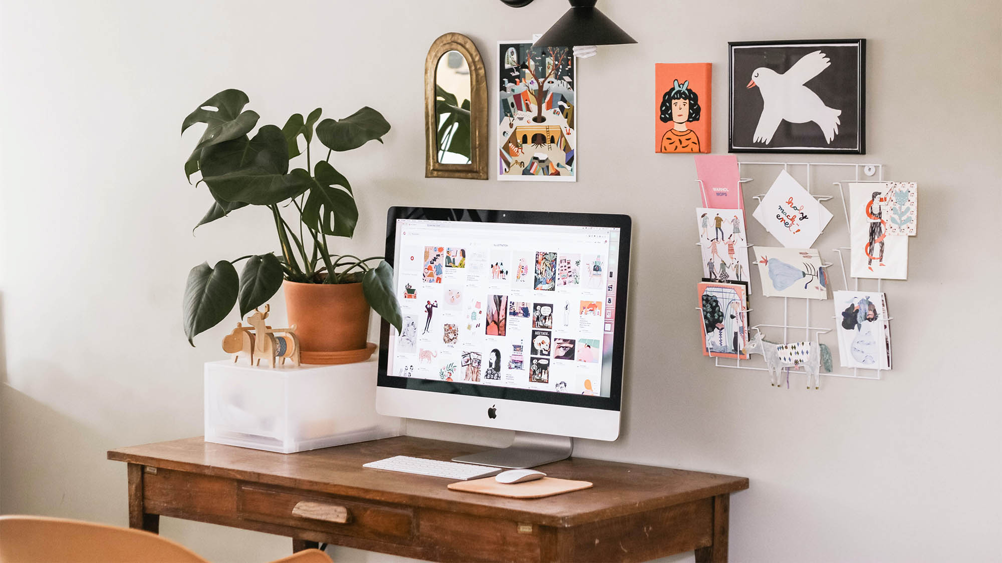 Wood desk with Mac monitor, houseplant and colorful wall art in background