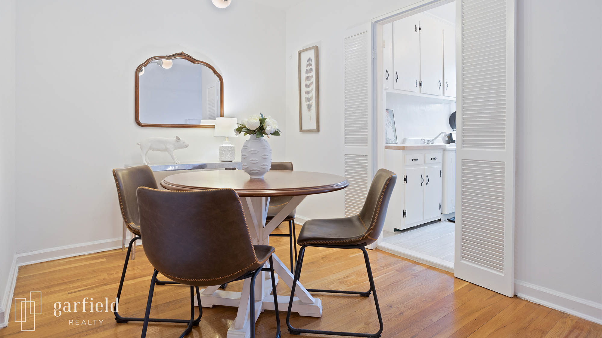 Staged dining room with four brown chairs and vase on table, wall mirror in background