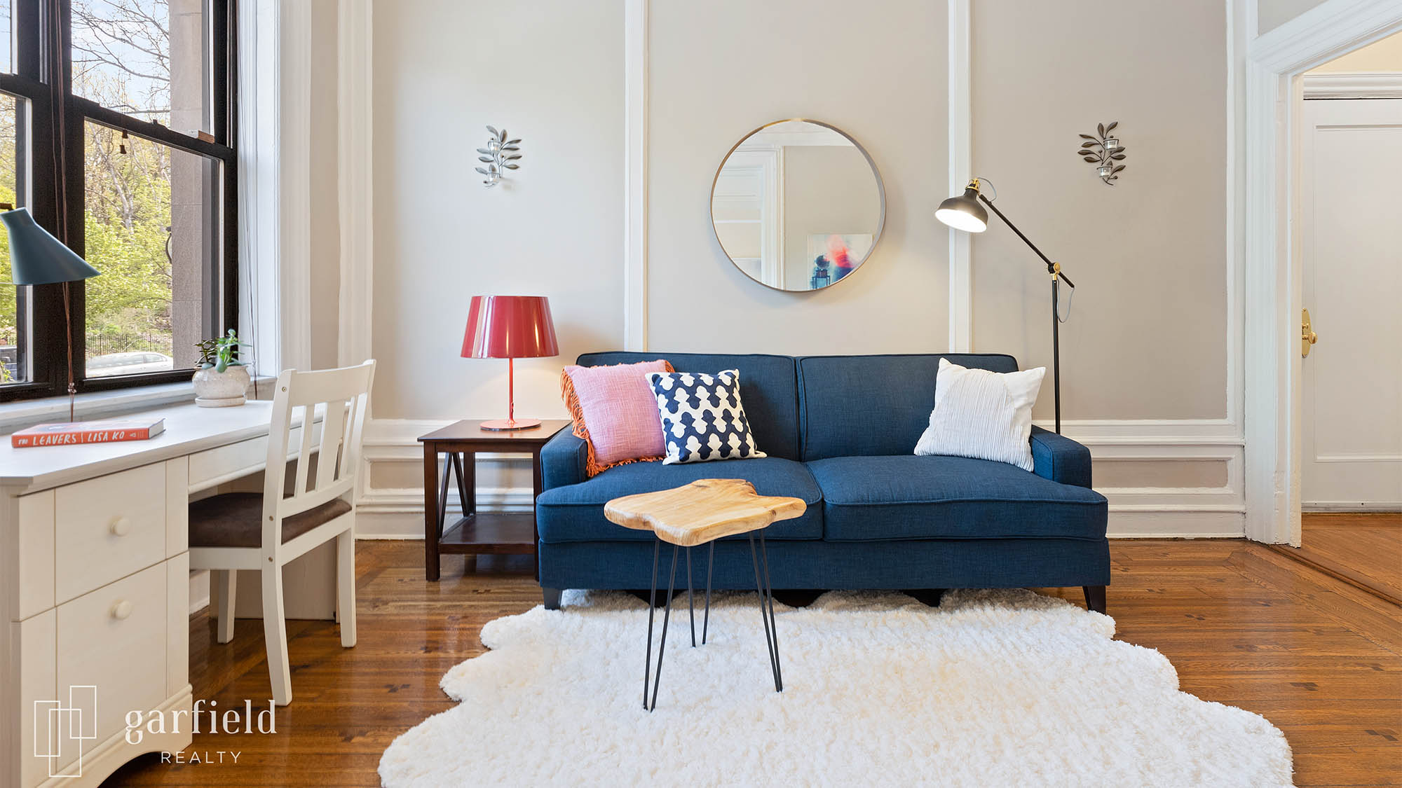 Staged living room with blue couch and modern decorative pillows with floor lamp to the right and coffee table to the left with red lamp and white desk and chair to the left against a window with white fur area rug and small wood table