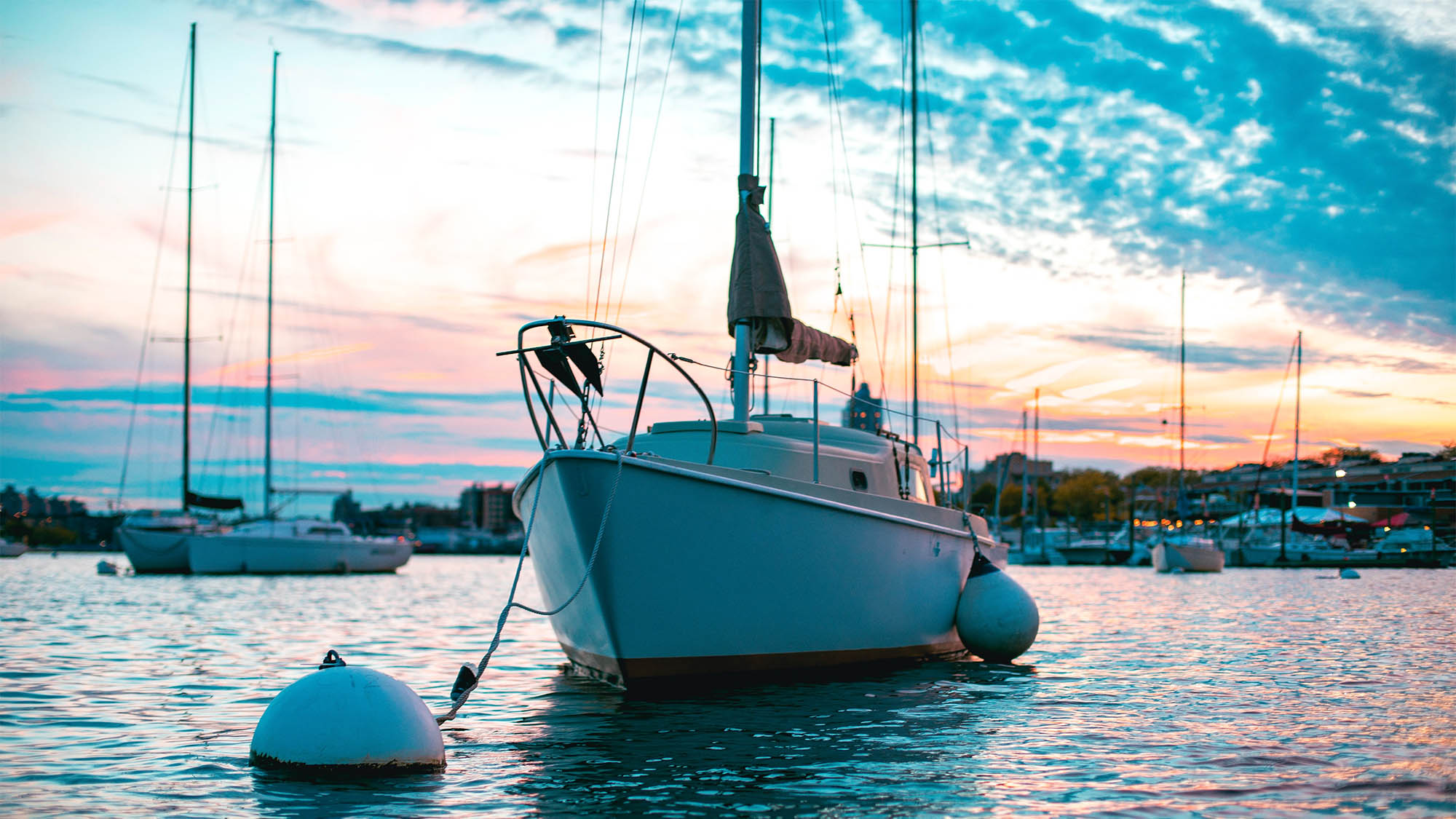 Docket boat beneath pink white and blue sunset sky