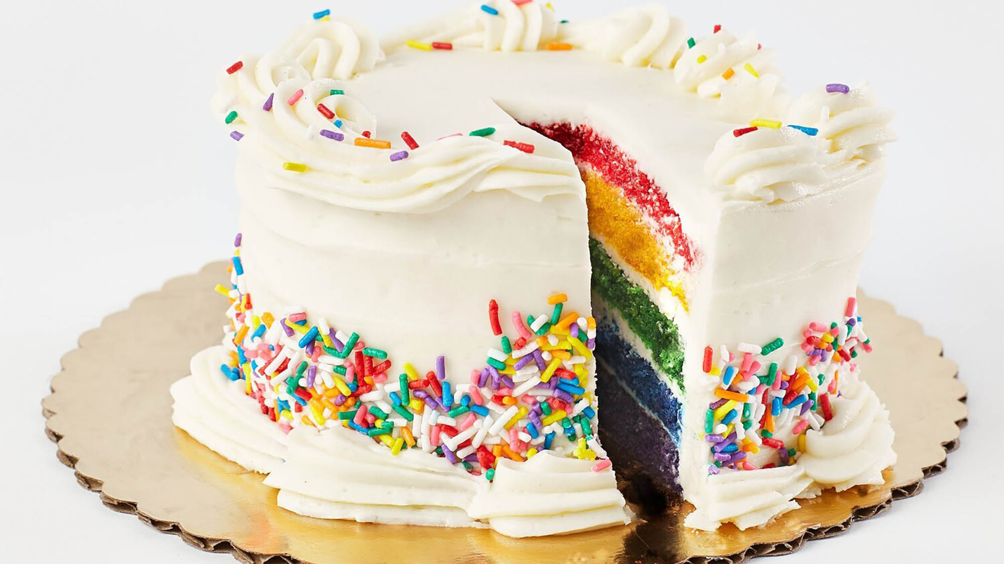 White cake with rainbow sprinkles with one missing piece revealing rainbow layers inside