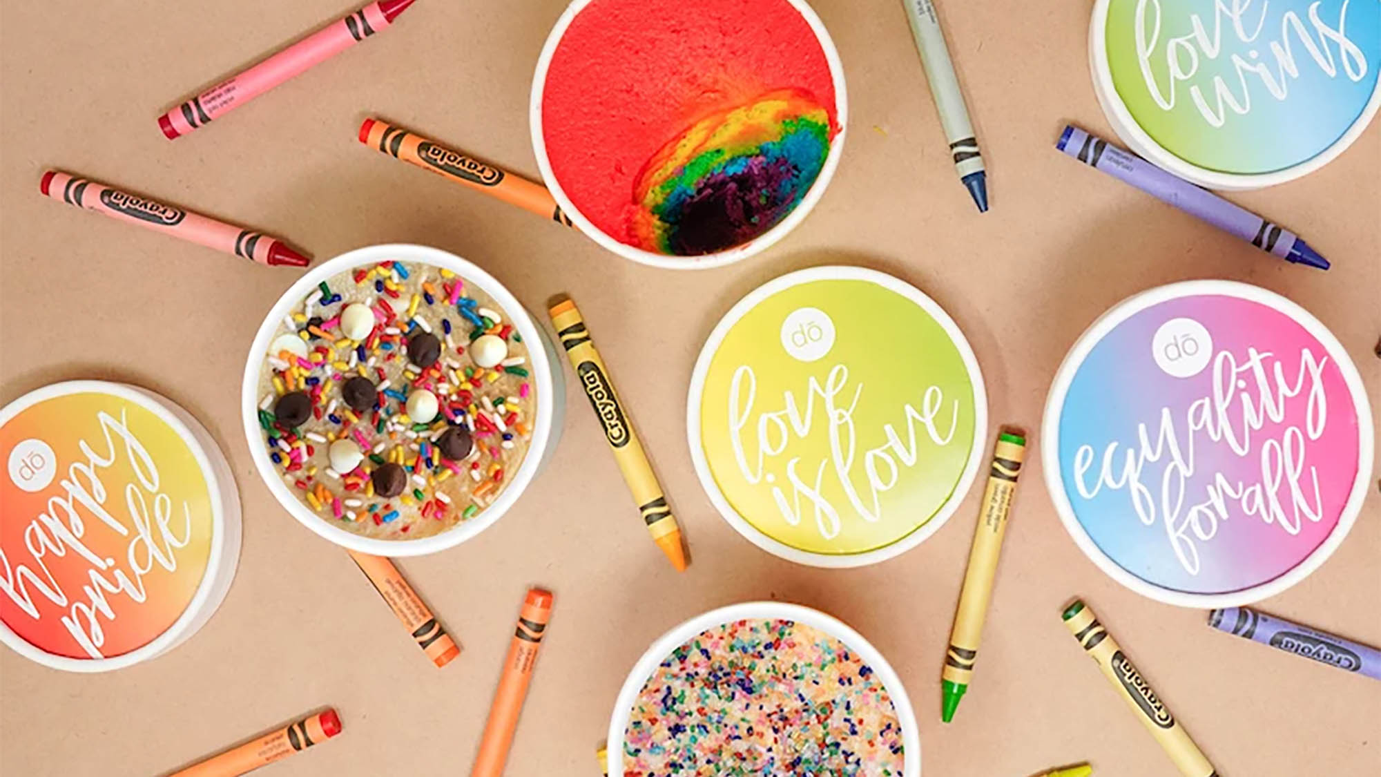 Rainbow edible cookie dough containers open and closed laid out with multicolored crayons on beige backdrop