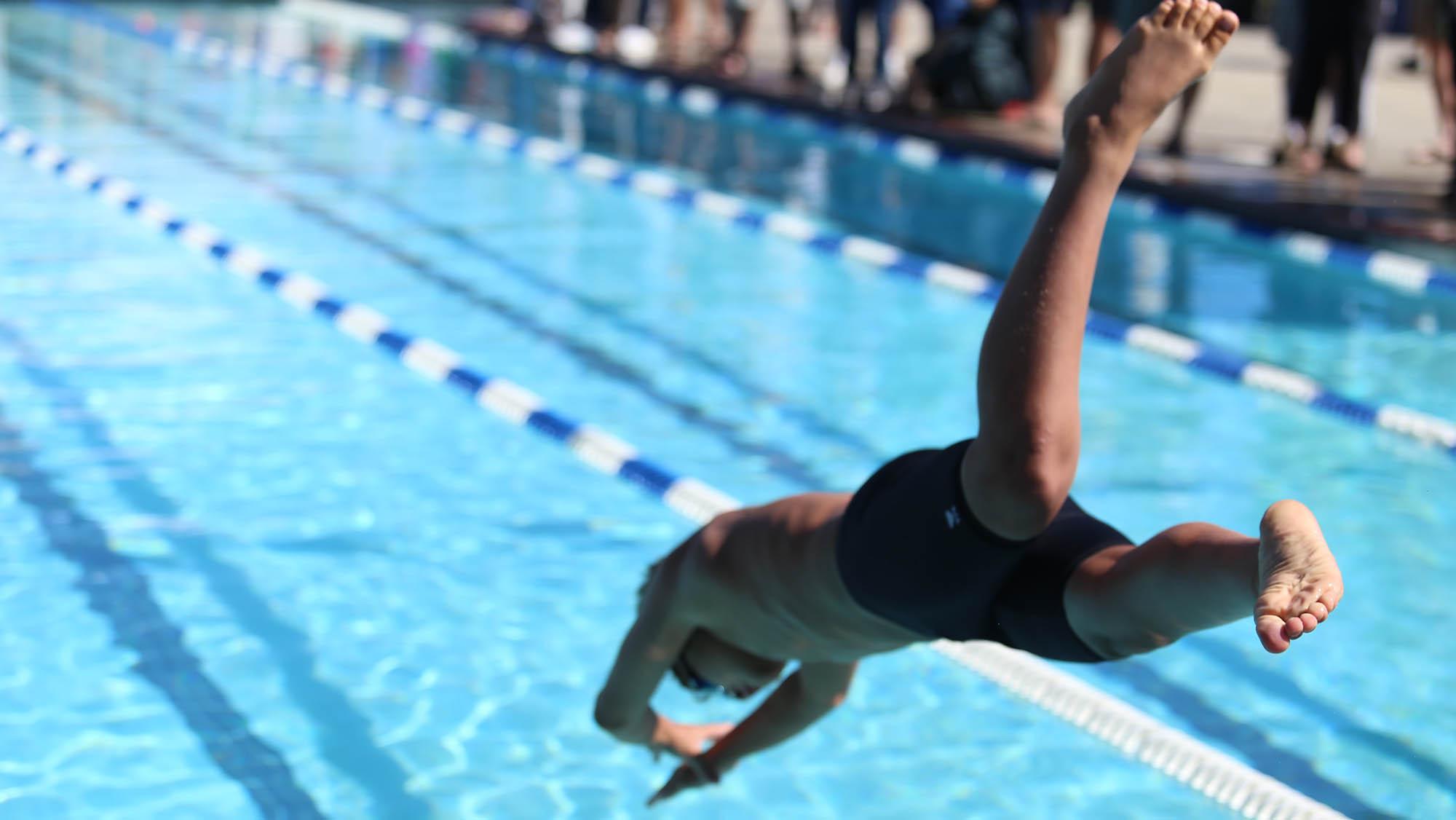 Boy diving into swimming pool lane