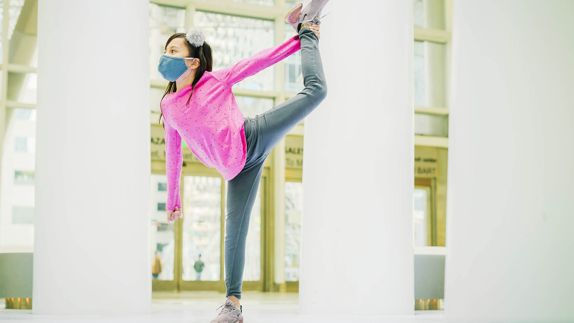 Masked girl dancing with pink shirt and grey pants