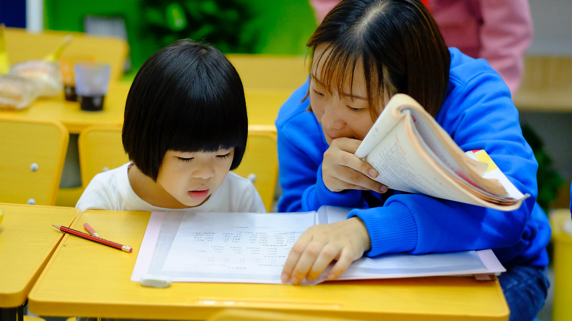 Asian woman tutoring Asian girl at desk