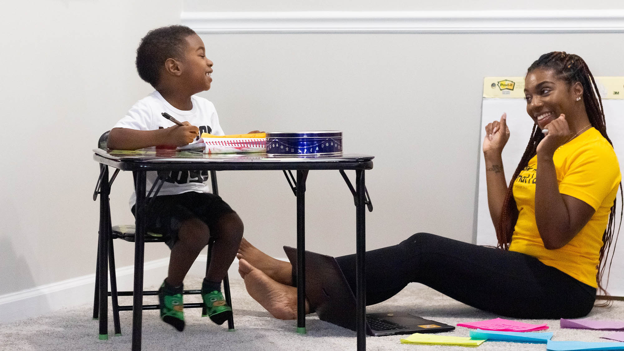 Black boy at table looking down at female Black teacher sitting on floor