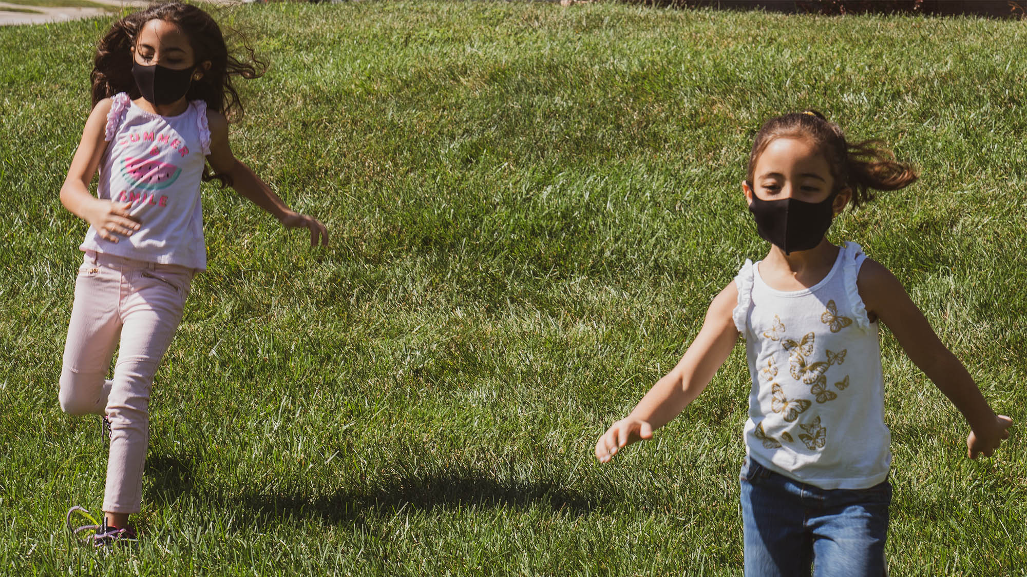 Two masked girls running in grass
