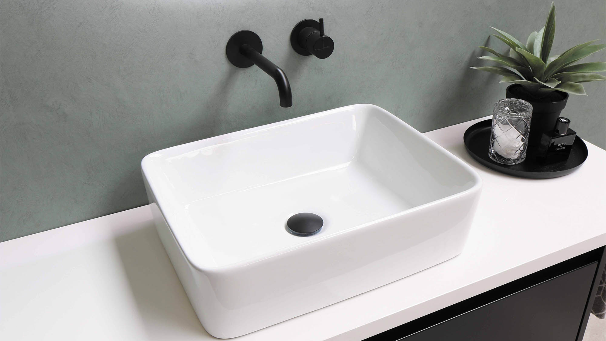 White bathroom sink with modern black wall faucet and succulent planter to the right