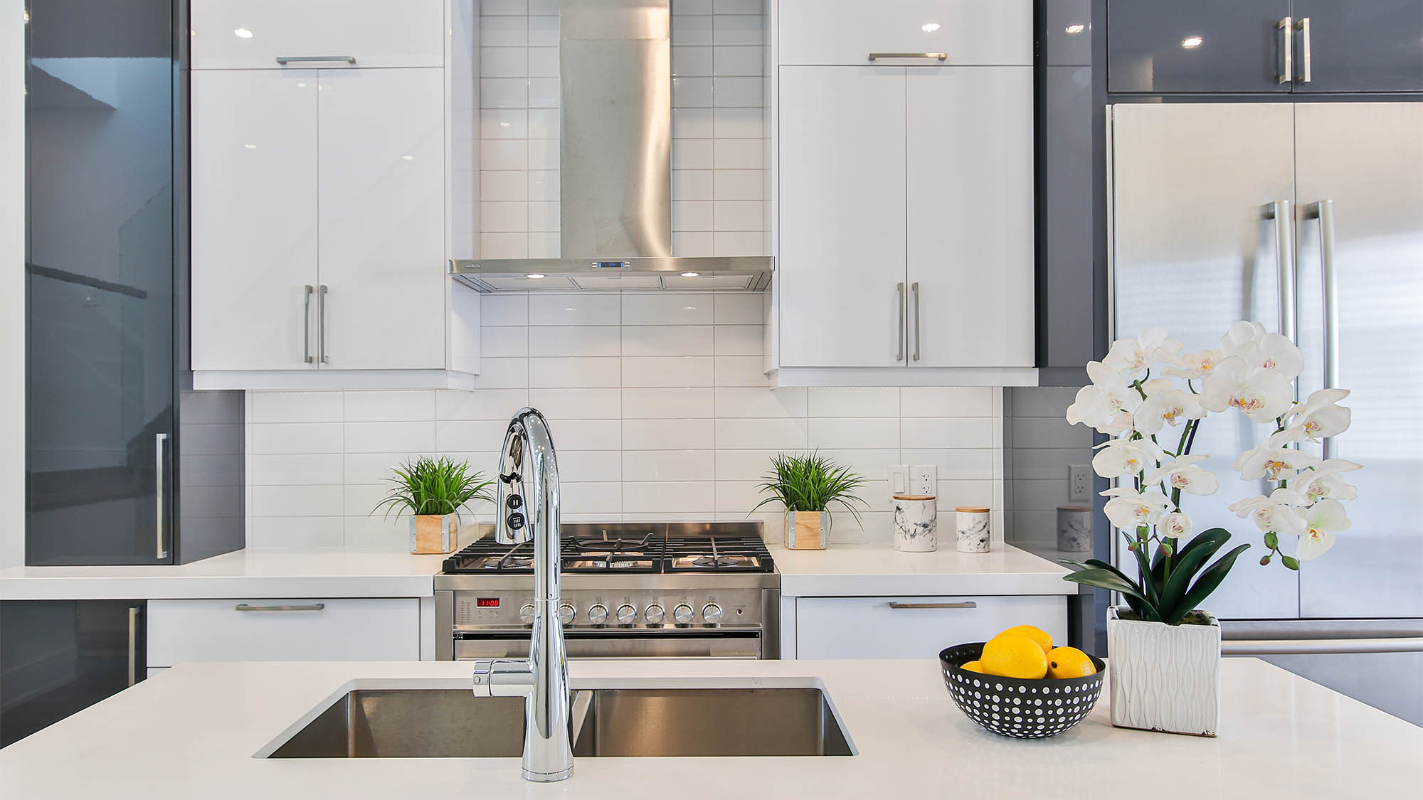 Stainless steel oven and hood flanked by white cabinets with white tile backsplash and view from over kitchen sink